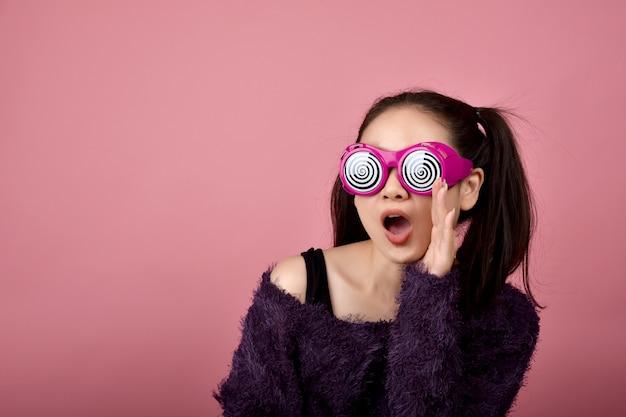 Удивленная азиатская женщина, крича девушка нося смешные стекла на изолированной розовой предпосылке, чувства стороны вау с космосом экземпляра для рекламировать.