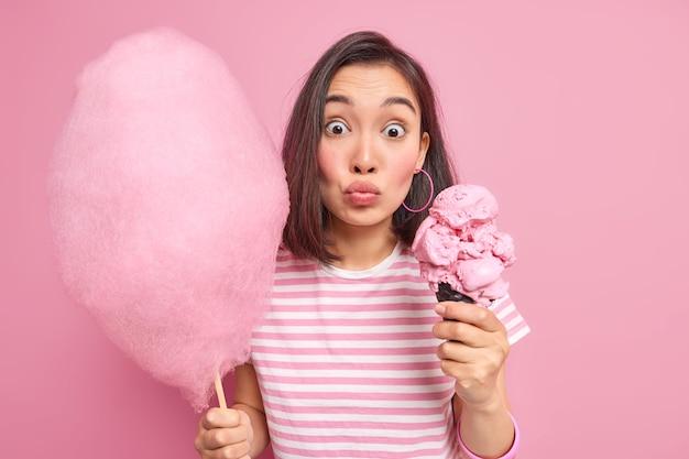 Удивленная азиатская женщина с темными волосами позирует с двумя восхитительными сладкими десертами, округляя губы, в повседневной полосатой футболке, изолированной на розовой стене. девочка-подросток держит вкусные аппетитные закуски