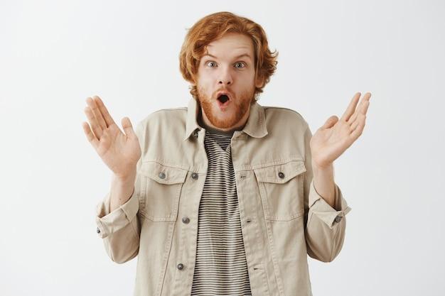 Ragazzo rosso barbuto sorpreso e stupito in posa contro il muro bianco