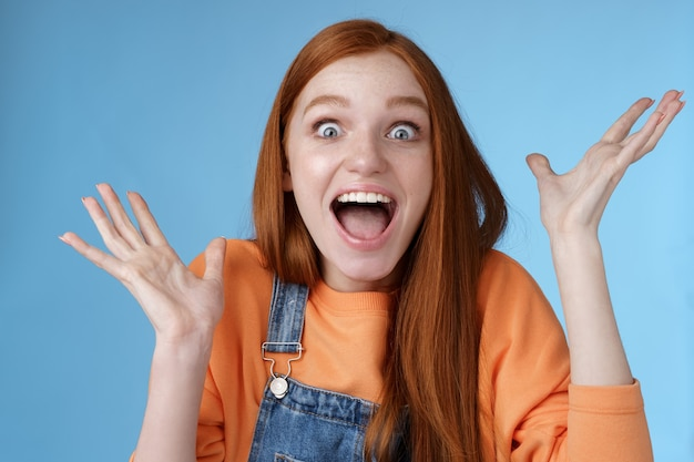 Surprised astonished sensitive overwhelmed young happy redhead girl receive incredible fantastic prize wide eyes astonished raising hands triumphing win lottery celebrating joyfully