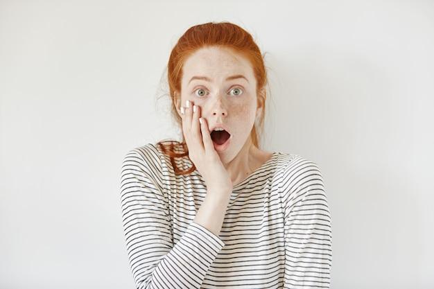 セーラーシャツを着て頬に触れ、口を大きく開いたままにして驚いた10代の少女は、予期せぬニュースでショックを受けました。怖いと恐ろしい探して忘れっぽい若い女性