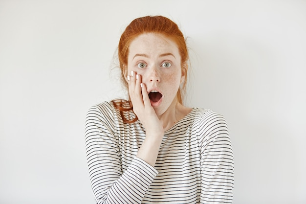 Surprised astonished teenage girl wearing sailor shirt touching her cheek and keeping mouth wide open looking shocked with some unexpected news. forgetful young woman looking scared and fearful