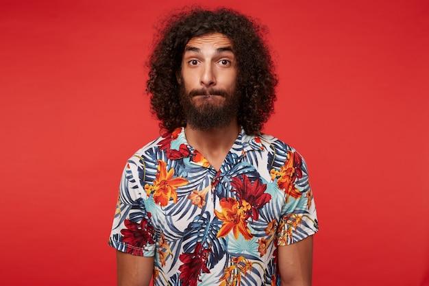 Удивленный привлекательный брюнет кудрявый парень с бородой, кусающий губы и смотрящий с поднятыми бровями, стоя, руки вдоль тела