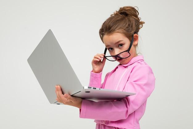 ピンクのスーツで驚いて魅力的な女の子は白いスタジオの背景にノートパソコンでニュースを読む