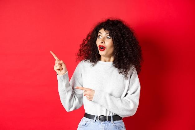 巻き毛、空のスペースを指して脇を見て、ロゴや広告を表示し、赤い背景の上に立っている驚きの魅力的な女の子