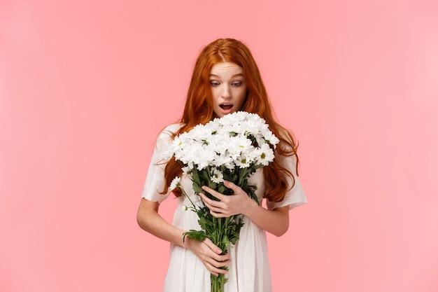Удивленная привлекательная рыжеволосая женщина получает романтический подарок на день святого валентина, глядя на красивый букет