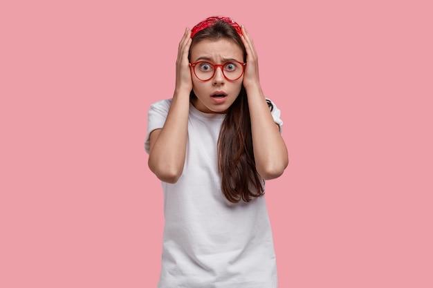 놀란 매력적인 여자가 머리에 손을 대고 공포를 쳐다보고 빨간 머리띠, 안경 및 흰색 티셔츠를 입습니다.