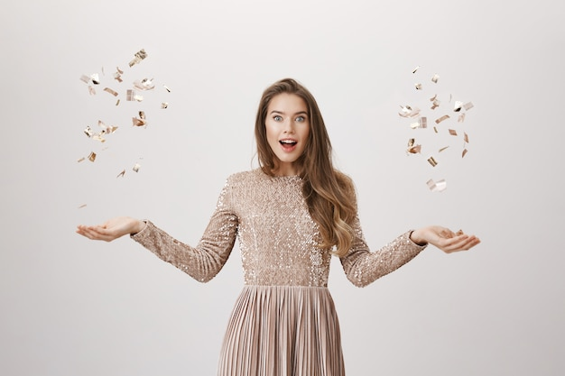 Surprised attractive woman tossing golden confetty in dress