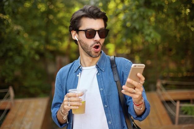 Giovane uomo barbuto attraente sorpreso in occhiali da sole in piedi sopra il parco verde con il cellulare in mano, ricevendo notizie inaspettate, indossando abiti casual