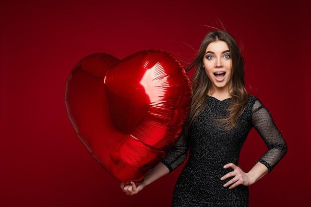 Удивленная привлекательная молодая девушка с воздушным шаром в форме сердца на красном