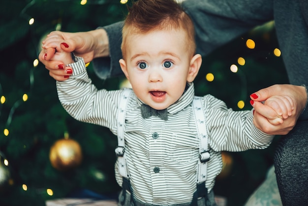 Удивленный мальчик в галстуке-бабочке и рубашке на фоне боке-огней елки