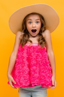 Surprised baby in a pink sweater and a straw hat on a  of an orange wall