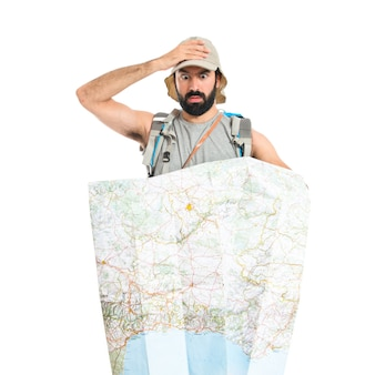 Удивленный backpacker с картой на белом фоне