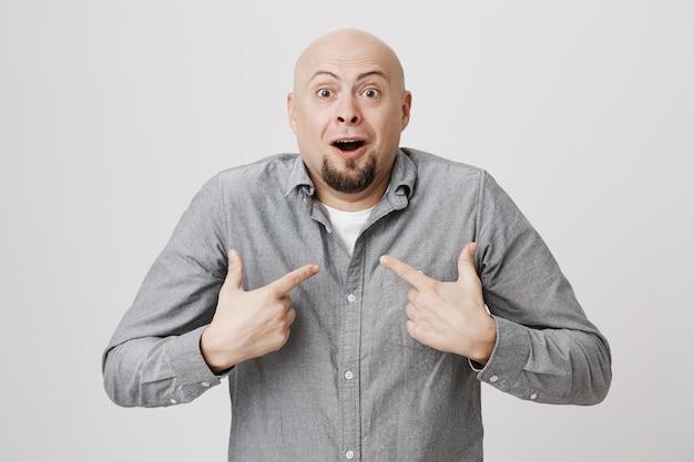 Uomo barbuto calvo sorpreso che indica se stesso eccitato