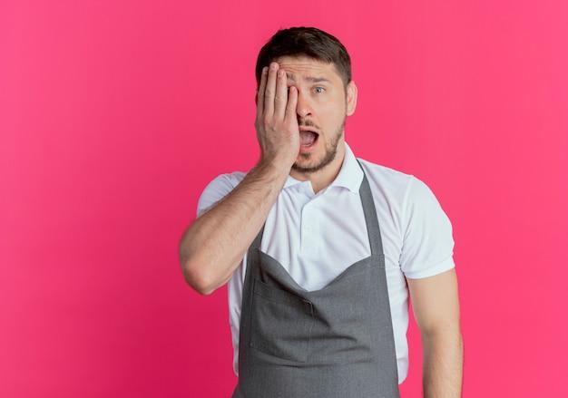ピンクの背景の上に立っている手で片目を覆っているエプロンで驚いた床屋の男