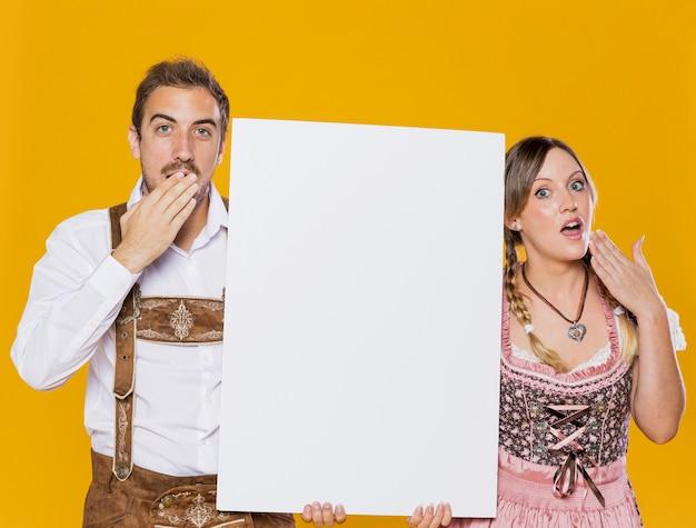 Удивленный баварский мужчина и женщина с макетом