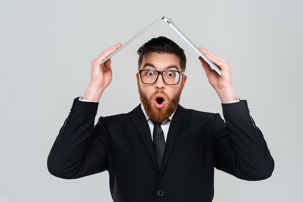 Surprised bearded business man in glasses and black suit holding laptop overhead