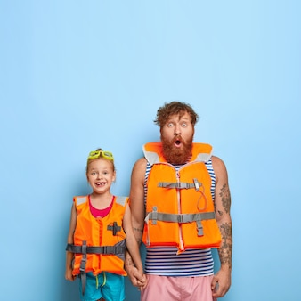 Surprised bearded dad with ginger beard, holds hand of little girl, wear protective lifejackets, ready for sea voyage, enjoy summer rest, stand against blue backgrond with copy space upwards