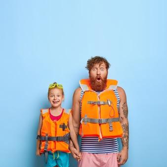 생강 수염을 가진 놀란 수염 난 아빠, 어린 소녀의 손 잡고, 보호 구명 조끼 착용, 바다 항해 준비, 여름 휴식 즐기기, 복사 공간이 위쪽으로 파란색 backgrond에 대항