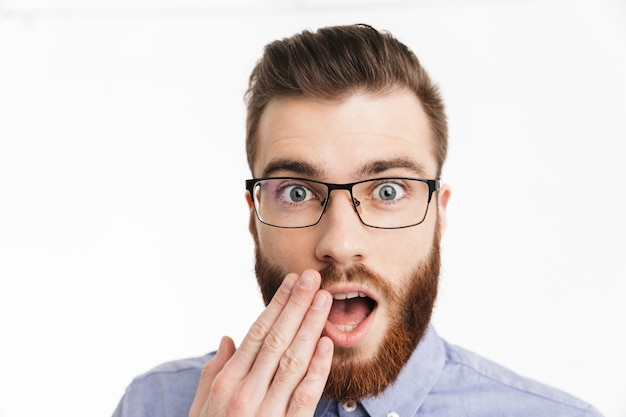 Удивленный бородатый элегантный мужчина в очках прикрывает рот и смотрит
