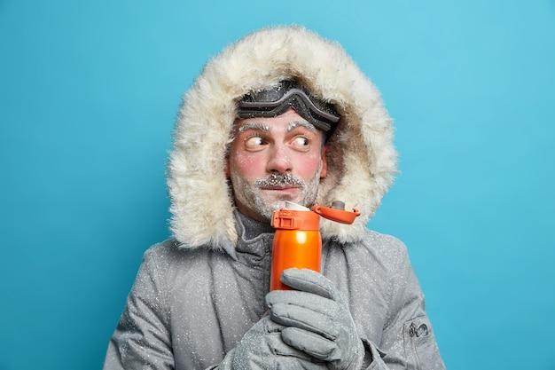L'uomo europeo barbuto sorpreso coperto di ghiaccio beve bevanda calda tiene thermos indossa occhiali da snowboard e giacca termica.