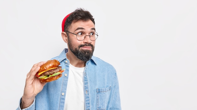 Surprised bearded european man focused away holds hamburger eats junk food wears round spectacles and denim shirt