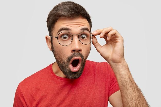 Il maschio barbuto sorpreso indossa una maglietta casual rossa e gli occhiali, apre la bocca mentre esclama con meraviglia, scioccato dai suoi doveri al lavoro, non si aspetta tale responsabilità, isolato sul muro bianco
