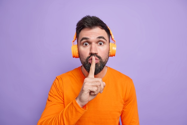 Удивленный бородатый мужчина просит помолчать, прижимает указательный палец к губам, рассказывает секрет, носит наушники, слушает любимую музыку, одет в оранжевый джемпер