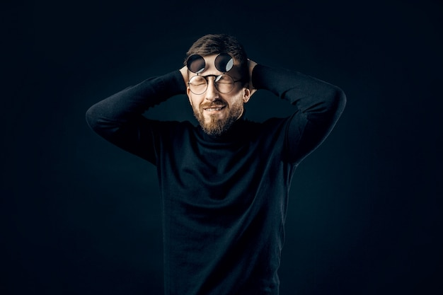 Surprised bearded man in black rounded glasses holding his head