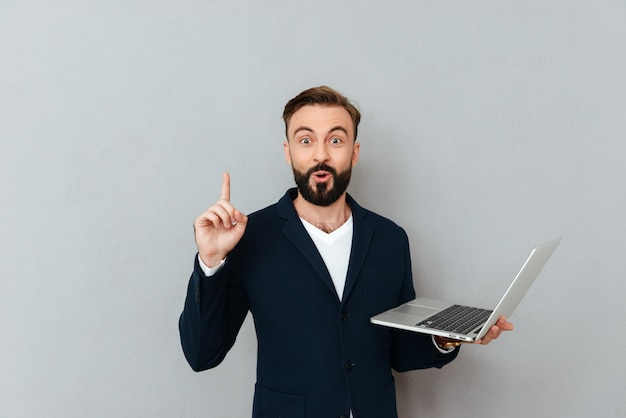 Surprised bearded man in busines clothes holding laptop computer and having idea while looking at the camera over gray