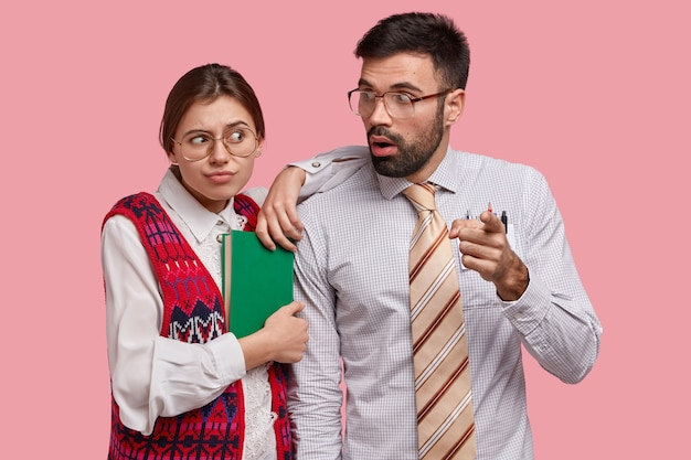 Surprised bearded man in formal wear with tie points forwards, shows something to groupmate who leans at shoulder, wears big spectacles, holds notepad, looks awkward, isolated on pink  wall