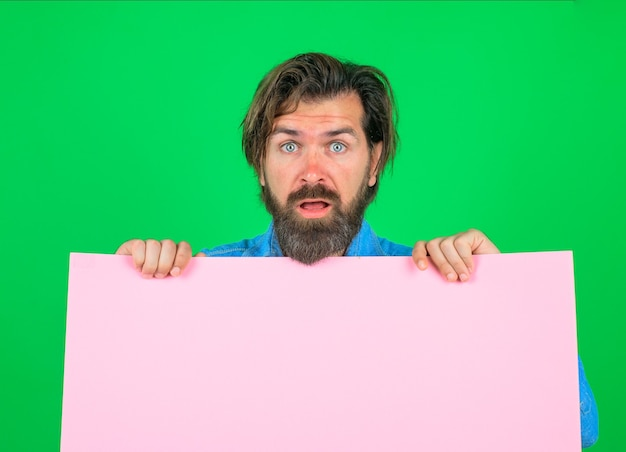Surprised bearded man holding advertising board advertising and sale online shopping advertising