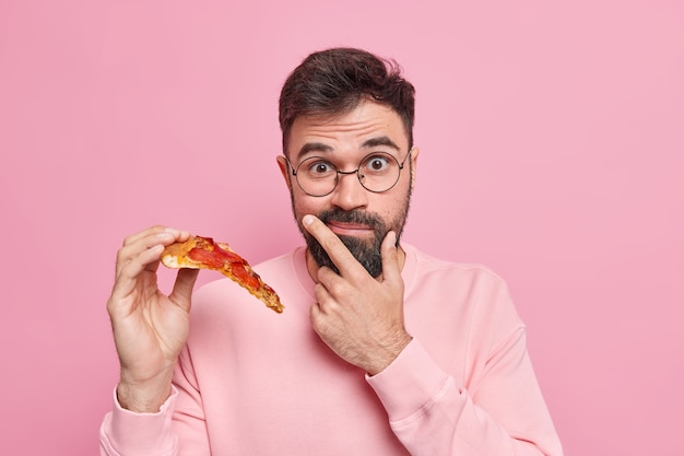 Surprised bearded man holds slice of pizza eats fast food has tasty snack for good mood wears round spectacles casual long sleeved jumper