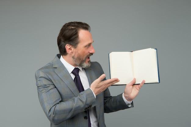 Удивленный бородатый мужчина в формальном деловом костюме показывает открытую книгу для информации, копировальное пространство.