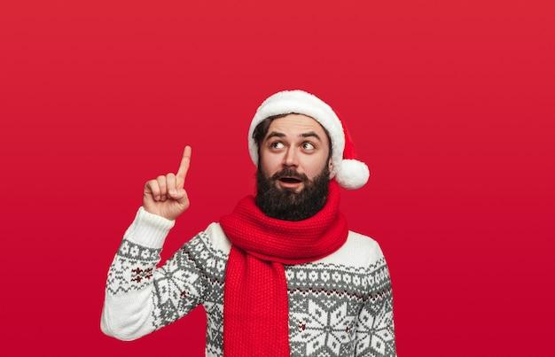 Удивленный бородатый мужчина в свитере и шляпе санты