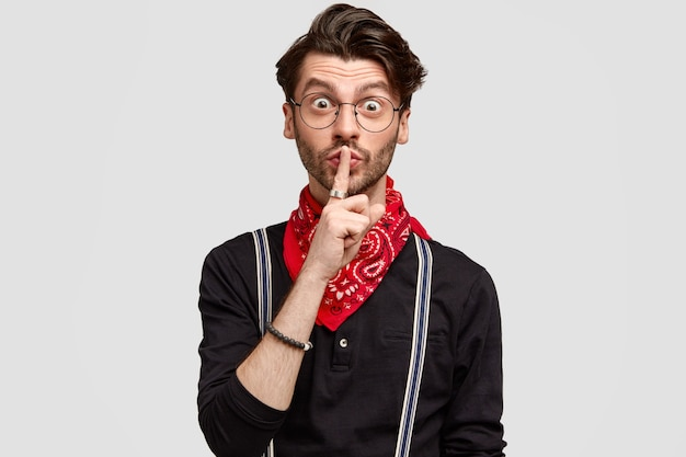 Surprised bearded man makes hush gesture, touches lips with index finger, wears stylish shirt with suspenders and red bandana, isolated over white wall