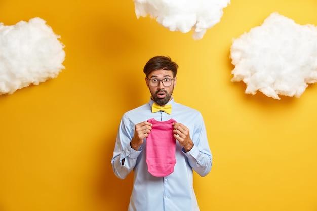 놀란 수염 난 남자는 아버지가 될 준비를하고 신생아를위한 바디 수트를 보유하고 나비 넥타이가있는 공식적인 셔츠를 입은 아기 탄생을 기다립니다.