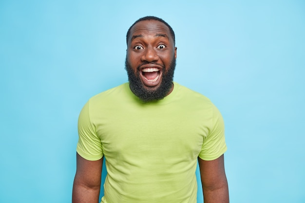 Surprised bearded man reacts on something unexpected keeps mouth opened dressed in casual green t shirt hears excellent news isolated over blue wall