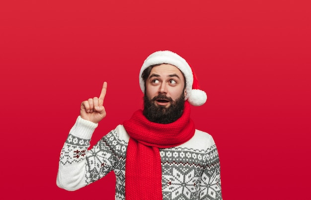 Surprised bearded man in sweater and santa hat