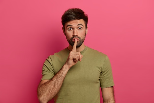 Surprised bearded man tells secret, keeps index finger on lips