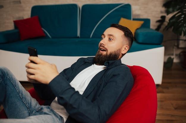 Удивленный бородатый мужчина с помощью смартфона дома.