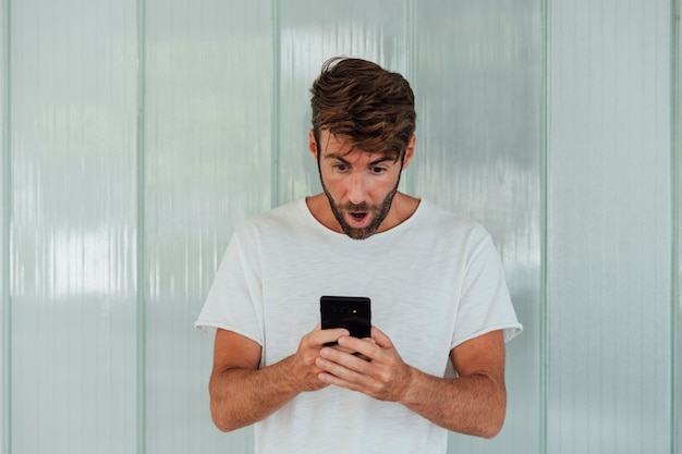Surprised bearded man with smartphone