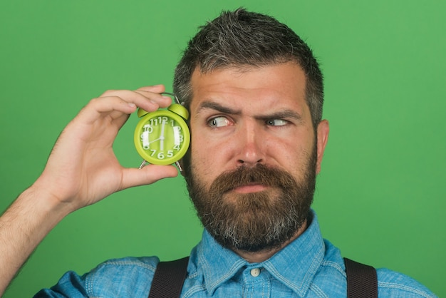 Surprised bearded man with stylish hairstyle in denim shirt holds alarm clock attractive macho with