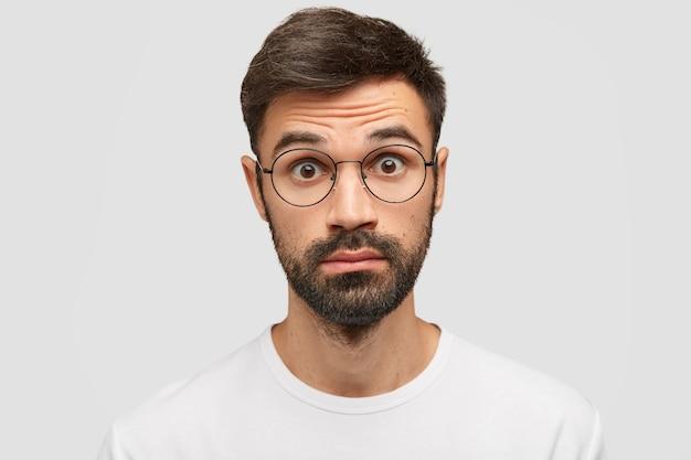 Uomo barbuto sorpreso con folta barba e baffi, guarda con espressione scioccata dopo aver sentito notizie di orrore
