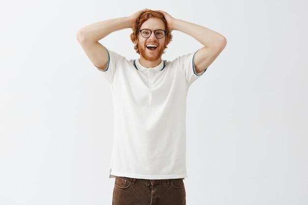 Ragazzo rosso barbuto sorpreso in posa contro il muro bianco con gli occhiali