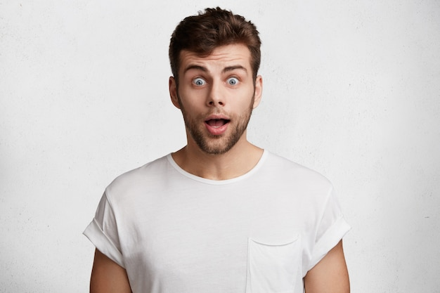 Удивленный бородатый молодой мужчина с голубыми глазами, одетый в повседневную белую футболку