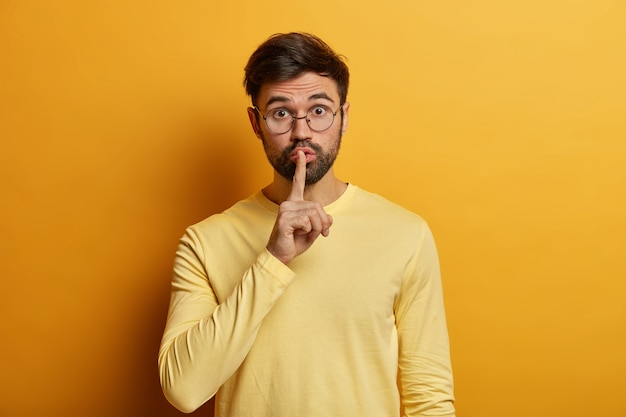 Surprised bearded young man presses index finger to lips, asks keep quiet, demands not spread secret, looks through optical glasses, looks secretly, wears yellow jumper. shh, be silent please