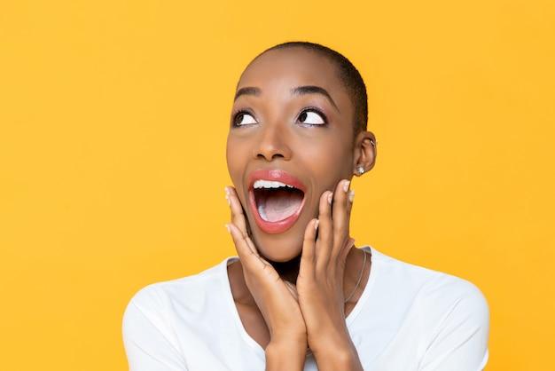あえぎと黄色の壁の空スペースに脇を見上げて美しいアフリカ系アメリカ人女性を驚かせた