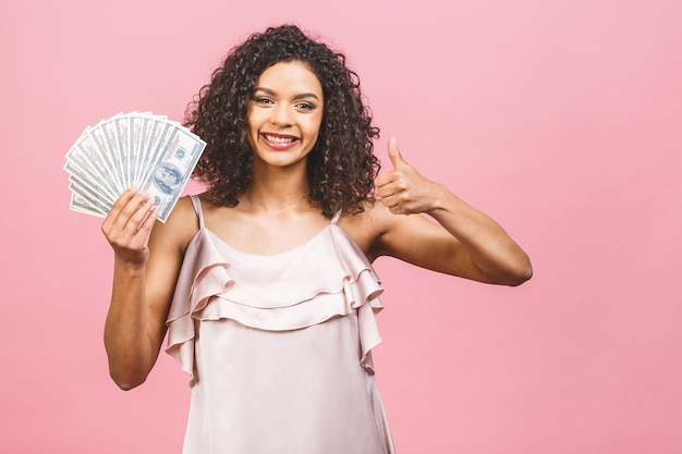 Удивленная красивая афро-американская женщина в платье держит деньги
