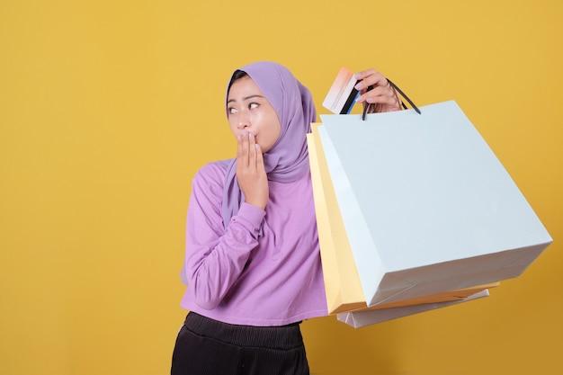 놀란 아름다운 아시아 쇼핑 중독 여성과 신용 카드 쇼핑 가방을 들고 뭔가를 가리키는
